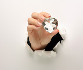 A female hand with a diamond, tearing white paper.