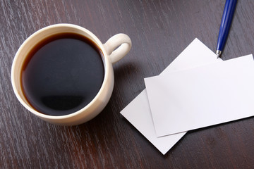 A cup of coffee and business cards on a desk