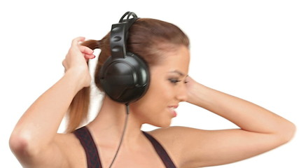 Beautiful lady listening music in large headphones, looking at c