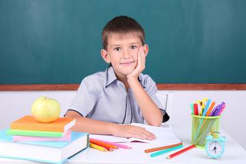 Schoolboy sitting in classroom on blackboard background