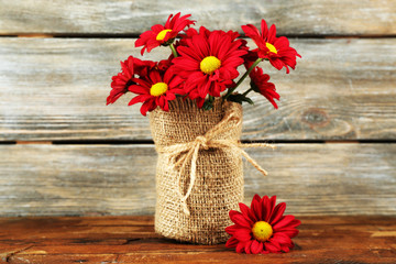 Beautiful chrysanthemum in vase on wooden background