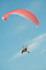 Extreme athletes paragliding in clear blue sky