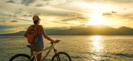Young woman with backpack standing on the shore near his bike.
