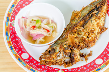 Fried mackerel fish on res-white dish (Thai foods)