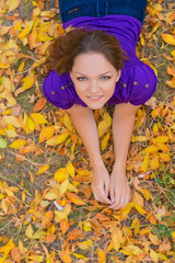 Young woman in violet shirt on autumn leaves