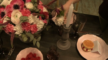 View of experienced florist decorates table