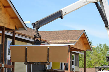 Telehandler moving plywood to a roof construction