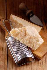 grattugia di acciaio e pezzo di formaggio parmigiano