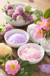 spa with pink herbal salt and wild rose flowers clover