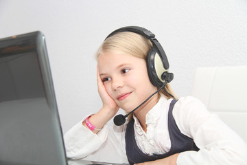 Llittle girl sits in front of a laptop with headphones