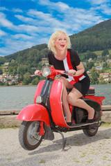 Junge Frau hat Spaß auf einem alten Motorroller