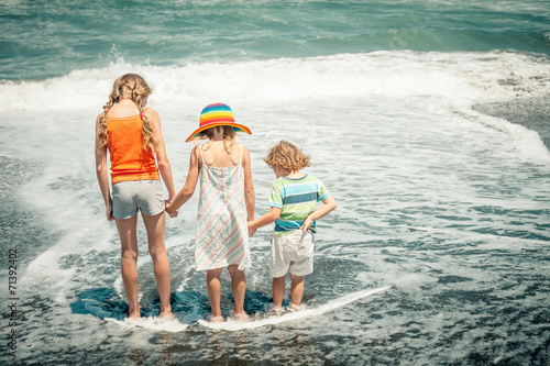 canvas print picture three happy kids playing on beach at the day time