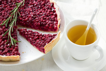 Red bilberry tart with a cup of herb tea