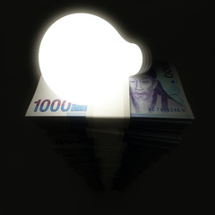 Money stack with shining lightbulb