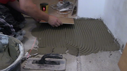 Master worker man lay ceramic floor tiles in kitchen