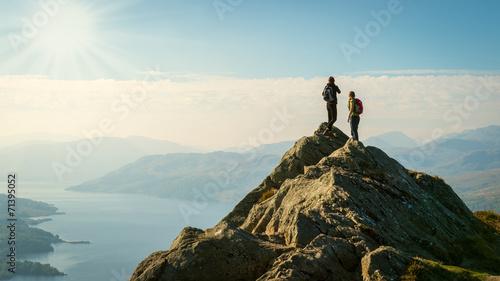 Leinwanddruck Bild hikers on top of the mountain enjoying view, Highlands, Scotland