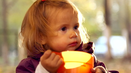 Child drinks tea in autumn park.