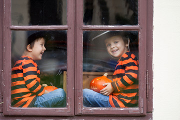 Two cute boys, sitting on a window with jack-o-lantern