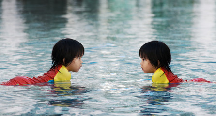 children play on water in swimimg pool