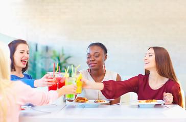 multiracial female friends having fun in restaurant