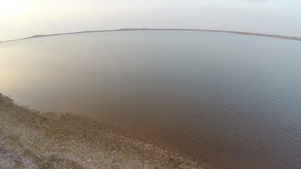 Aerial view. Flying over a large lake, evening, sunset