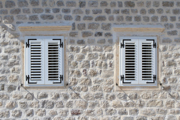 Two shuttered windows in the stone wall of the house