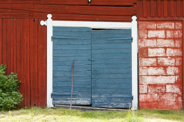 Red painted barn with two blue painted doors