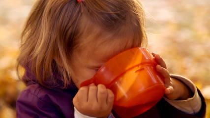 Little girl drinks tea with emotionally mugs.