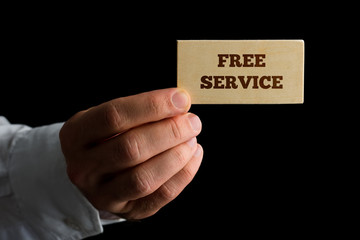 Man holding a card announcing a Free Service