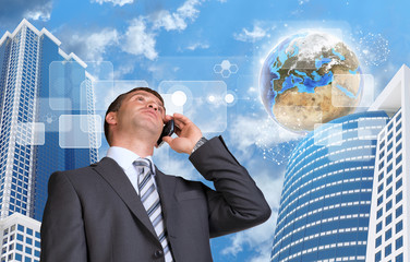 Businessman talking on the phone. Skyscrapers and Earth with
