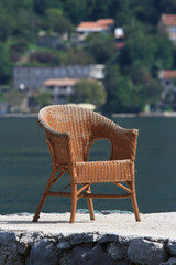 old wicker chair on a background of the sea bay. close-up