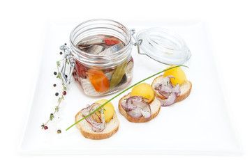 pickled herring in a glass jar with potato canapes