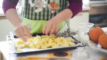 close up of woman housewife hands cooking baked potatoes