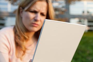 frau schaut zornig auf tablet