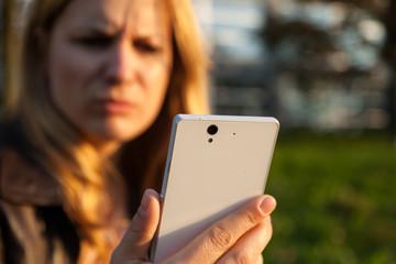 frau mit grimmigem blick und smartphone