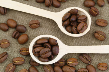 Coffee beans on wooden spoons, close up