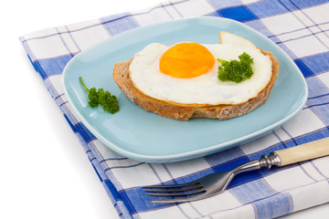 fried egg in blue plate with fork, over white background