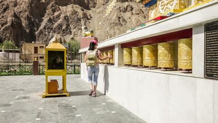 Woman traveler turns Tibetan Buddhist prayer wheels.