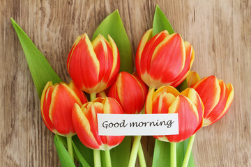 Good morning card with red and yellow tulips on wooden surface