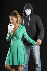Anonymous Couple with masks isolated on black background