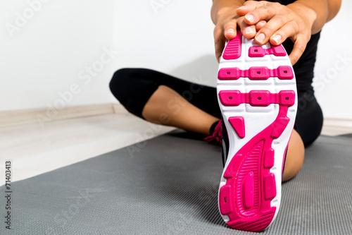 Tuinposter Gymnastiek Woman stretching in a gym