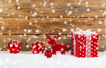 red gift for christmas on a wooden background with snow