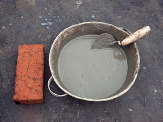 Цементный раствор, мастерок и кирпич