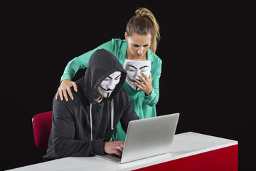 Masked Anonymous Hacker with girlfriend in front of a laptop