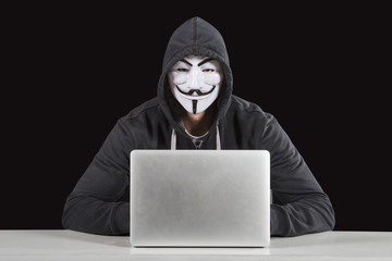 Masked Anonymous Hacker in front of a laptop isolated on black