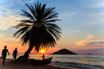 Sunset with palm tree and boat at the beach in africa
