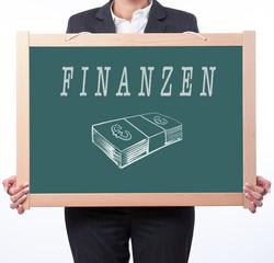Tafel mit dem Wort Finanzen und Geldscheine Symbol