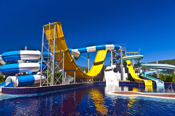 Blue, white and yeloow waterslide in a pool.
