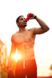 Athletic build dark skinned man drinking water after run