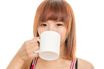 Asian woman drinking from white coffee cup